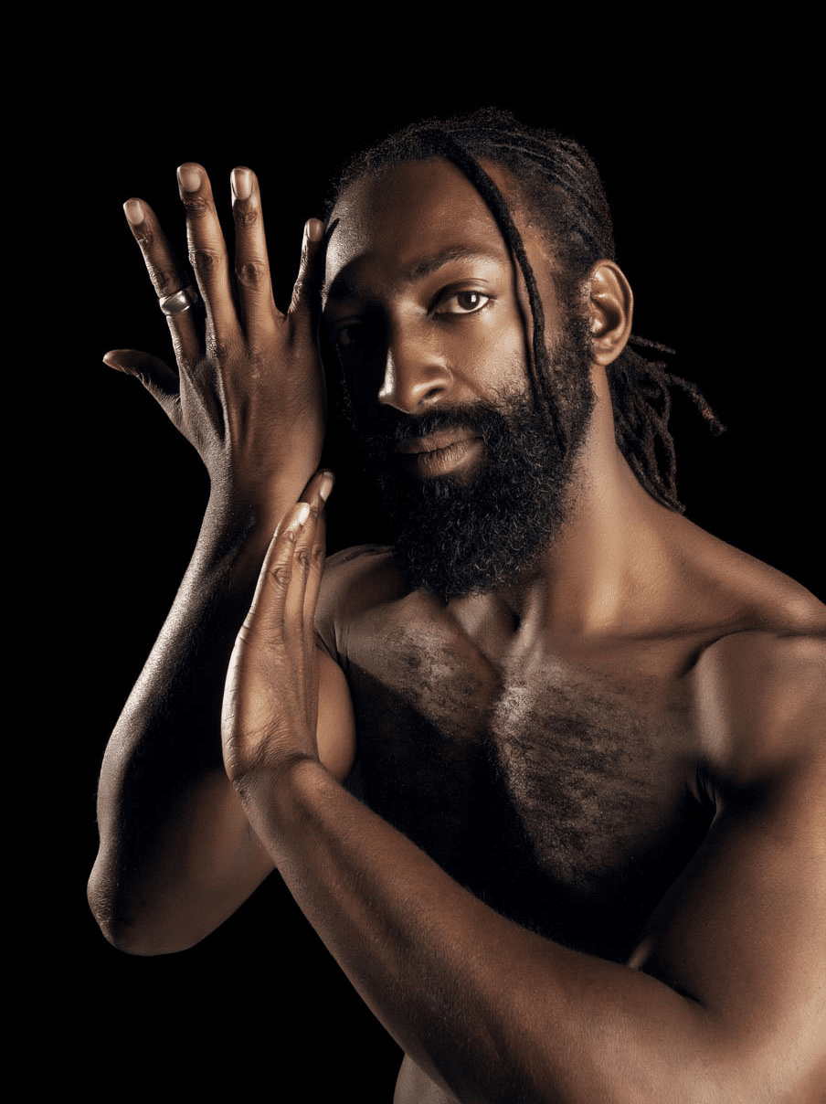 African American man standing against a black background looking into the camera, shirtless with a chiseled body, full beard and his dreads are tied in a low ponytail, he is holding his arms up to the left side of his face with one hand pressing on the lower part of his other hand that is outstretched