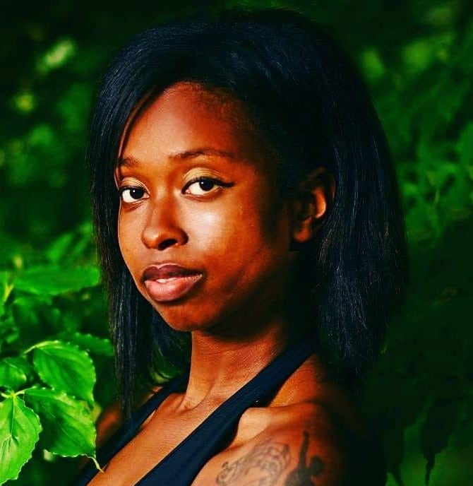 African American woman with shoulder legnth straight hair looking into the camera against a nature background with a tattoo on her shoulder