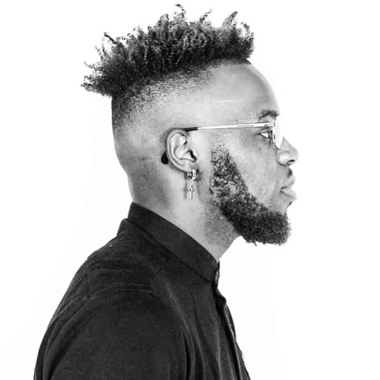 Black and white photo of a bearded black british man looking to the right, wearing glasses and a dangle earring